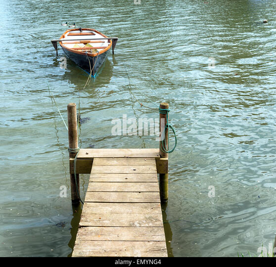 A small rowing boat moored to a wooden jetty on the banks of the Tresillian river in Cornwall - Stock Image