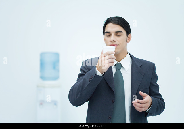 Businessman holding and smelling disposable cup with eyes closed, water cooler in background - Stock-Bilder