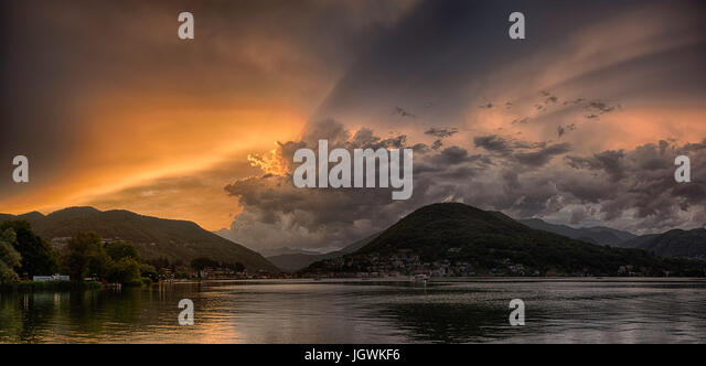 Sunset over the Lugano Lake in a end of the summer day with cloudy sky and ray of sunny light - Stock Image