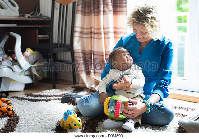 Woman playing with her adopted baby boy - Stock-Bilder
