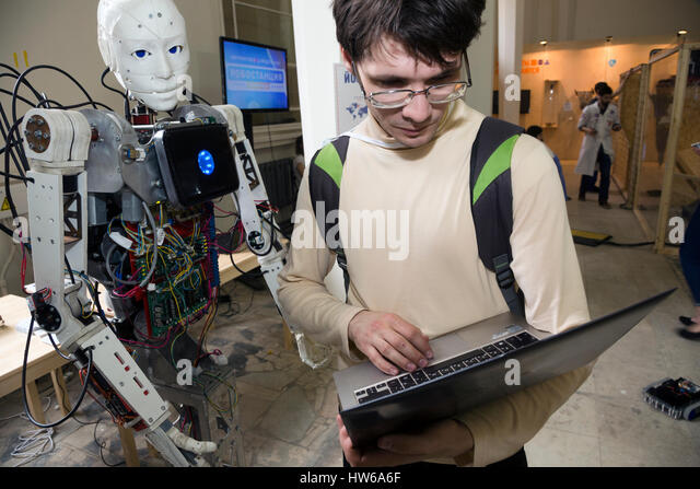 A young scientist testing an anthropoid robot at the Robostation, at Moscow's VDNKh Exhibition Center in Russia - Stock-Bilder
