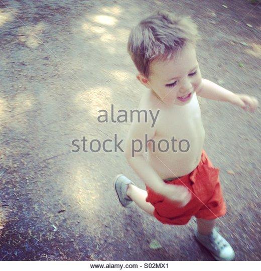 Small boy running shirtless - Stock Image