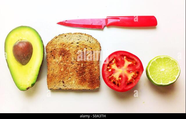 Making of a vegan/vegetarian open sandwich with avocado, tomato and whole wheat bread toast. - Stock Image