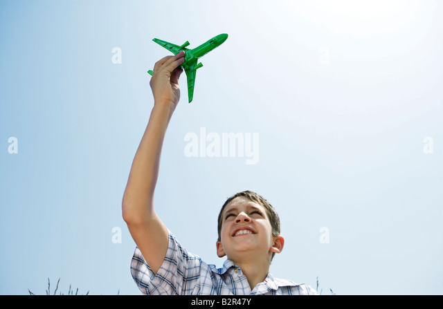 Boy holding toy plane aloft - Stock Image