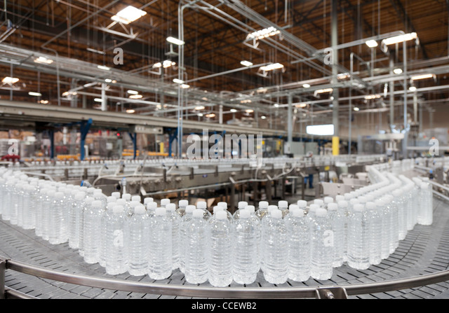 Bottled water on conveyor at bottling plant - Stock Image