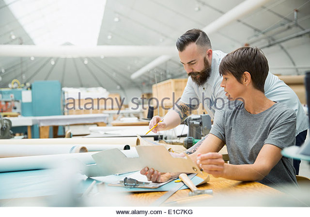 Workers examining form in textile manufacturing plant - Stock Image