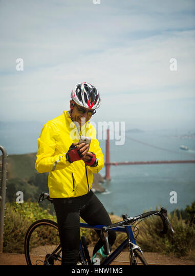 Hispanic man on bicycle texting on cell phone at waterfront - Stock-Bilder