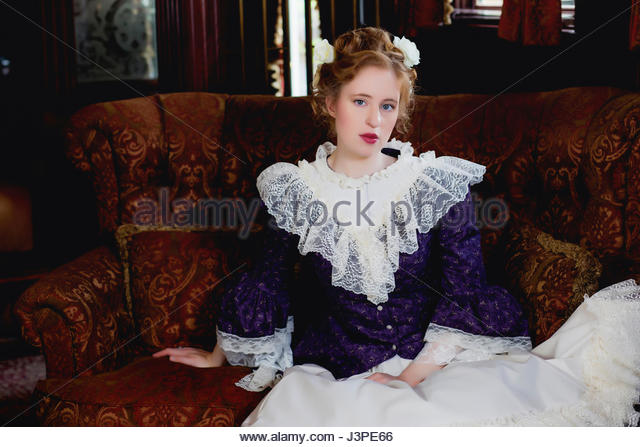 Victorian woman sitting on a sofa - Stock Image