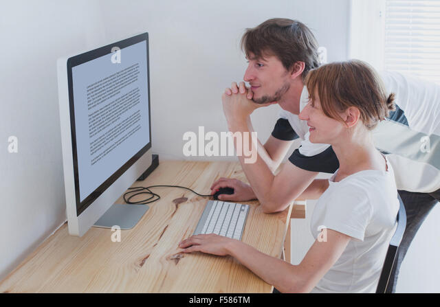 young couple looking at computer at home - Stock Image