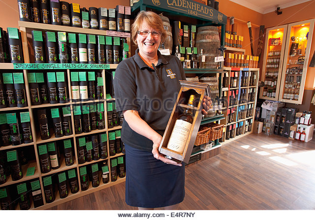 The shop assistant poses for a photograph with a bottle of 1919 single malt whisky valued at £50,000 at the - Stock-Bilder