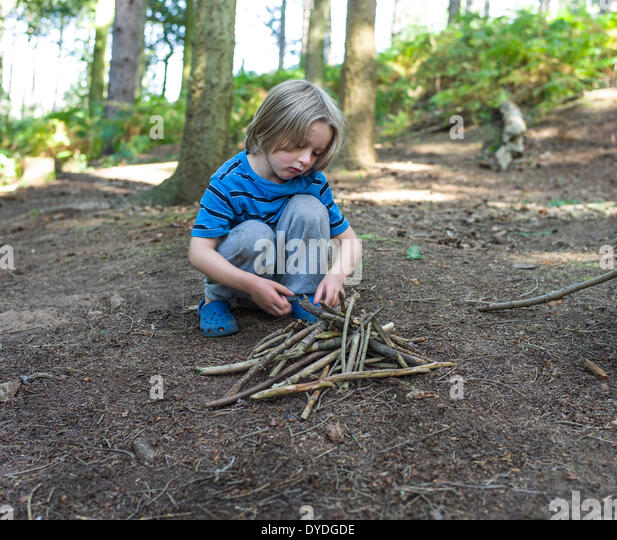 A young boy building a fire in the woods. - Stock Image