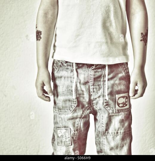 Torso of child in Jeans with tattoos - Stock-Bilder