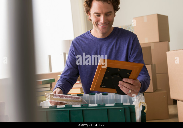 Mature man unpacking picture frame from crate - Stock-Bilder