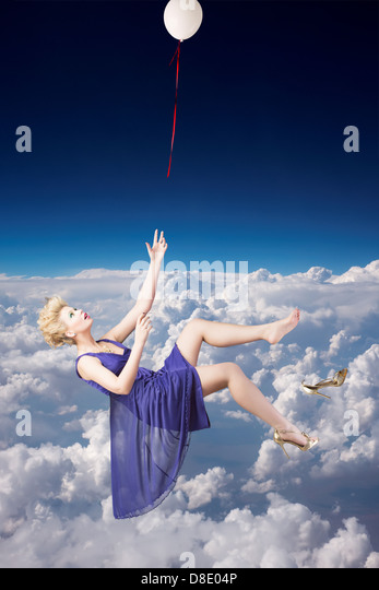 Beautiful woman falling down from the sky - Stock Image