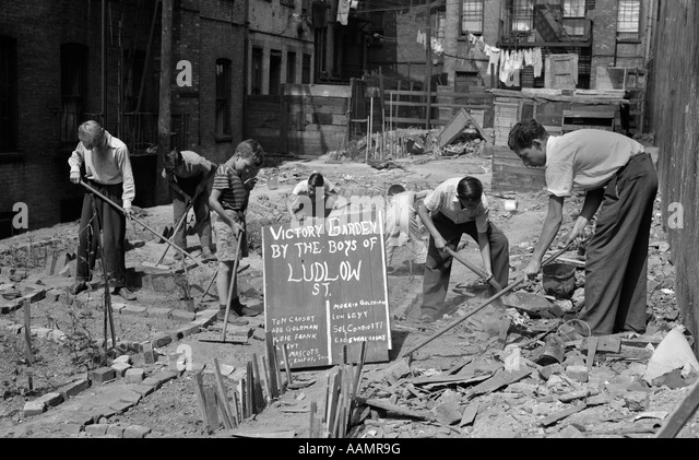 1940s BOYS WORKING IN WARTIME VICTORY GARDEN LUDLOW STREET NEW YORK CITY LOWER EAST SIDE MANHATTAN WWII - Stock Image
