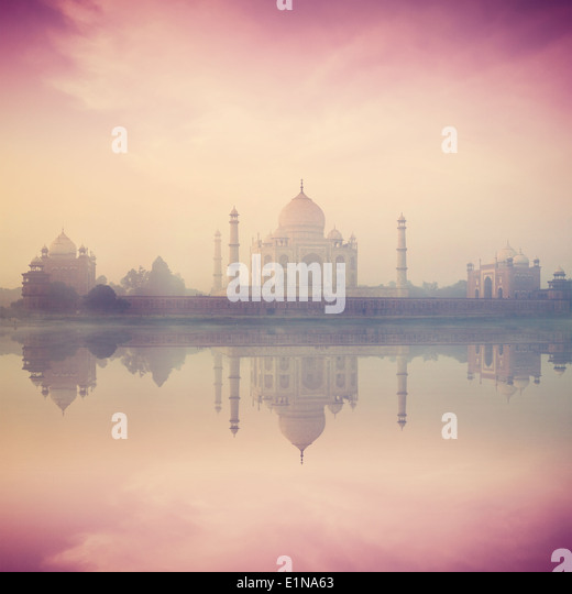 Vintage retro hipster style image of Taj Mahal on sunrise sunset reflection in Yamuna river panorama in fog, Indian - Stock Image
