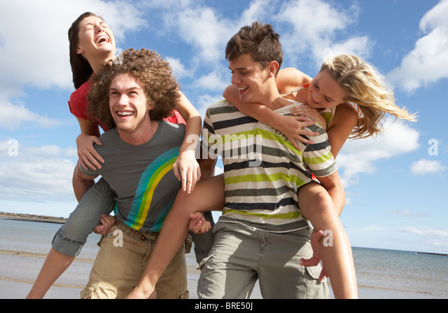 Group Of Young Friends Having Fun On Summer Beach Together - Stock Image