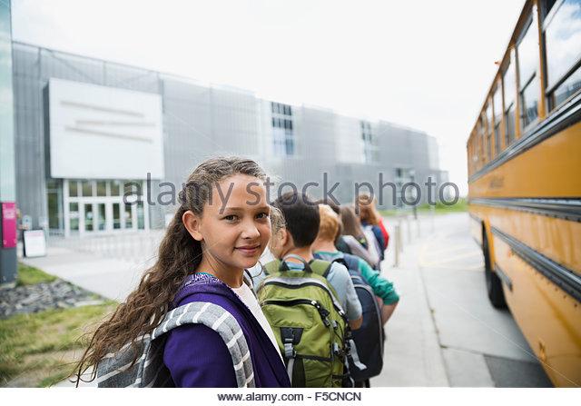 Portrait smiling schoolgirl arriving science center with classmates - Stock Image
