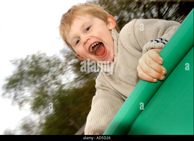 Hyperactive boy on roundabout in play park - Stock Image
