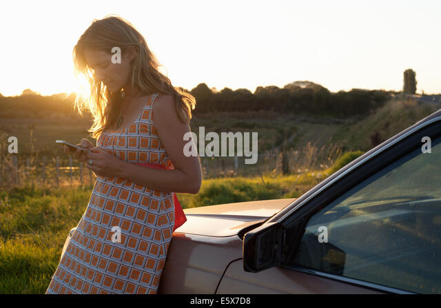 Mid adult woman leaning against car texting on smartphone - Stock Image