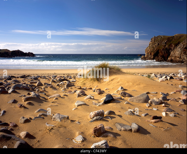 View out to the Atlantic Ocean from a remote rock covered sandy beach on the west coast of the Isle of Lewis. - Stock Image