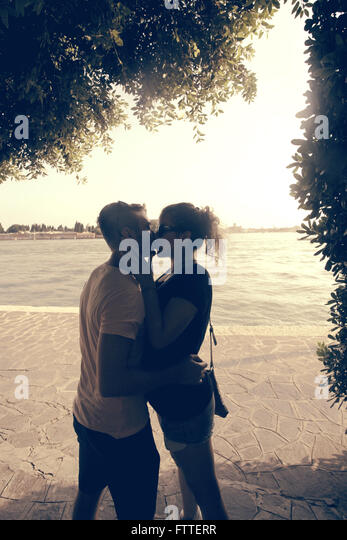 Young couple kissing in the shade - Stock Image