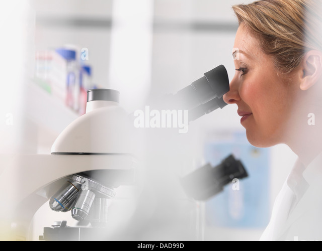 Female microbiologist viewing specimen under microscope in lab - Stock Image