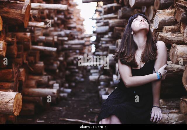Woman Sitting On Woods Looking Up Holding Arms Outdoors - Stock Image
