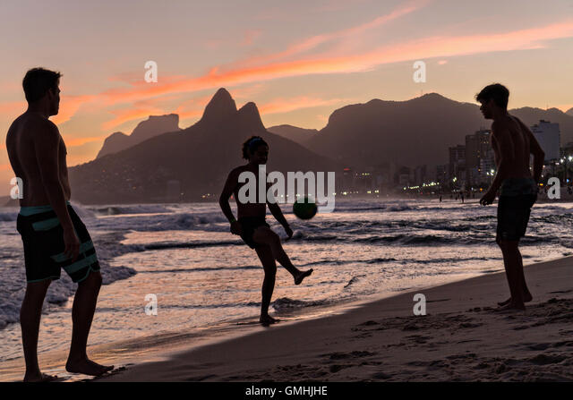 Young men play football on Ipanema beach silhouetted by sunset with the Two Brother mountains in the distance in - Stock Image