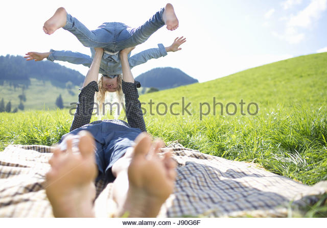 Father Balancing Daughter On Arms In Countryside Field - Stock-Bilder