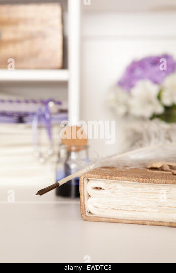 Nostalgic fountain pen lying on a handmade book - Stock Image