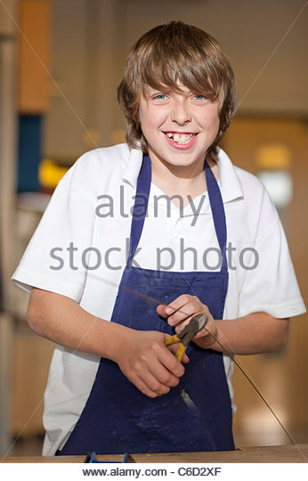 Portrait of smiling boy using pliers to cut wire in school workshop - Stock Image