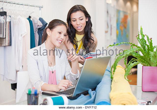 Fashion designers using laptop in office - Stock-Bilder
