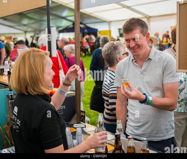 Visitor to the Ludlow Food Festival sampling Oldfields cider, Shropshire, England, UK - Stock Image