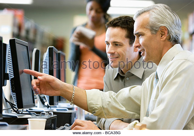 Businessmen looking at computer monitor - Stock Image