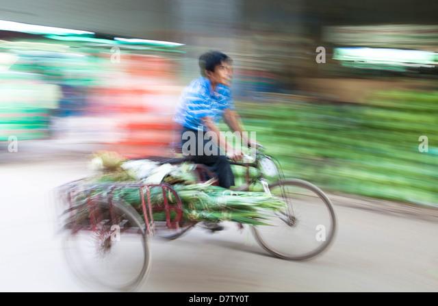 Panned and blurred image to add a sense of movement of a man cycling through Thiri Mingalar market, Yangon (Rangoon), - Stock Image