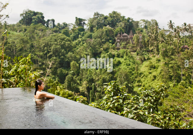 Asian female guest in infinity pool of private pool villa at Ubud Hanging Gardens, Bali, Indonesia. The infinity - Stock-Bilder