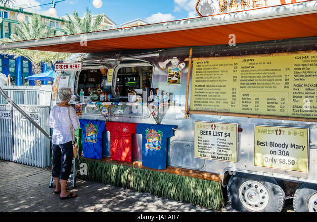 Mature woman buying lunch at a popular food truck in Seaside, Florida, a beach resort near Destin, on Scenic Highway - Stock Image