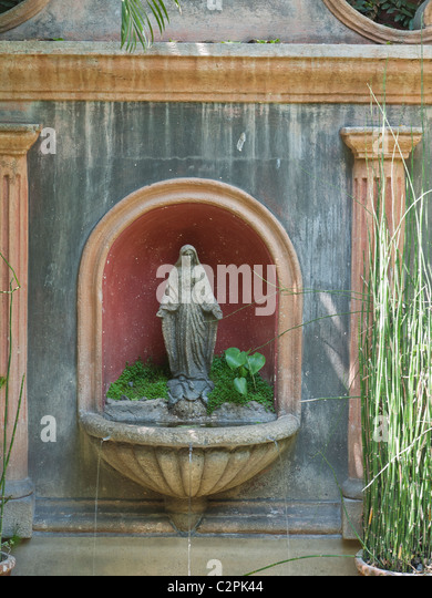 Vertical image of a fountain with statute of Virgin Mary in hotel patio in Antigua, Guatemala. - Stock Image