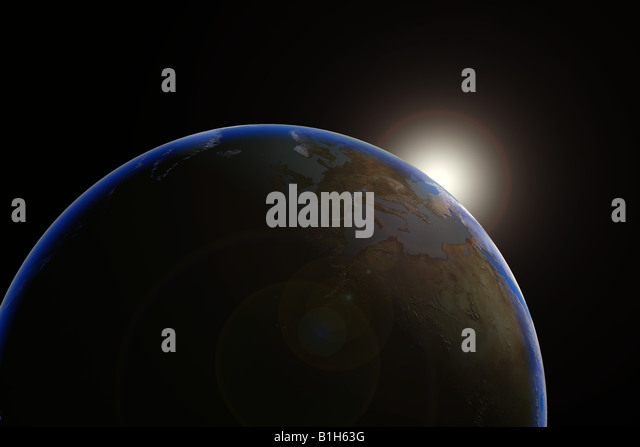 Sun emerging over planet earth - Stock Image