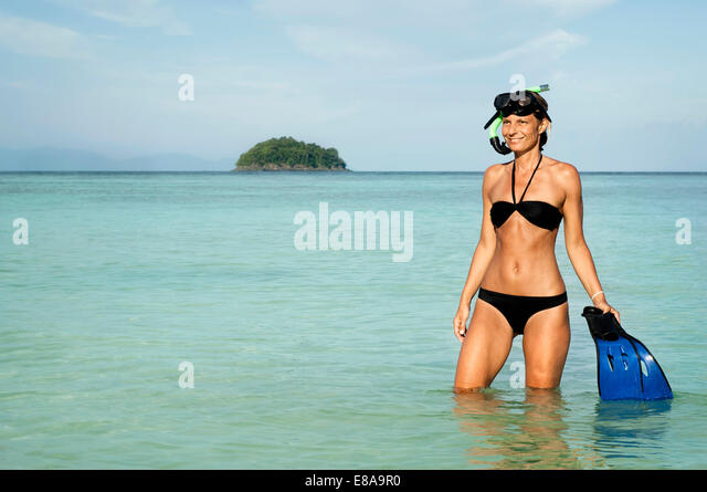 woman with snorkeling equipment standing in the water, Koh Lipe, Thailand - Stock Image