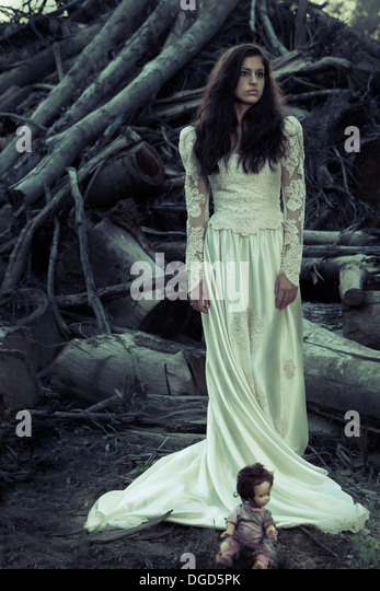 Woman in antique wedding dress with cut down trees and creepy doll - Stock Image