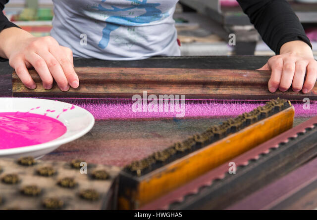 Block printing, hands pressing woodblock on color on felt mat, woodblock and plate with color in front, Bad Aussee, - Stock Image