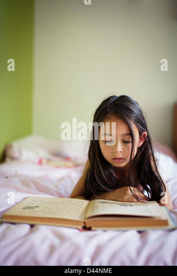 Girl lies in bed reading book - Stock Image