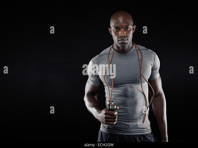 Handsome muscular man with jumping rope on black background. Fit African model with lots of copy space. - Stock Image