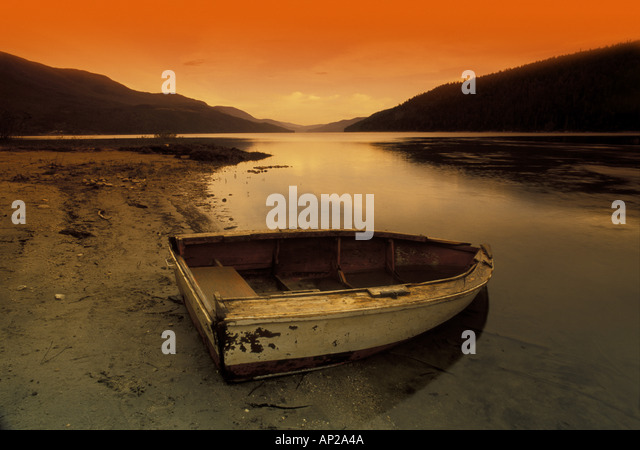 Row boat at water's edge against sunset backdrop - Stock Image