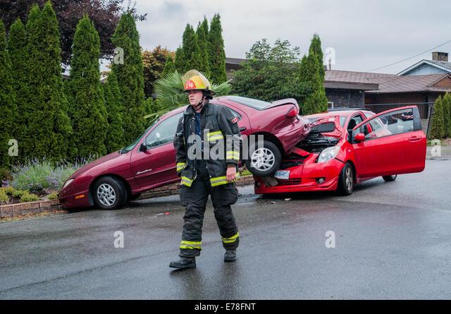 Firemen at  car accident scene. - Stock Image