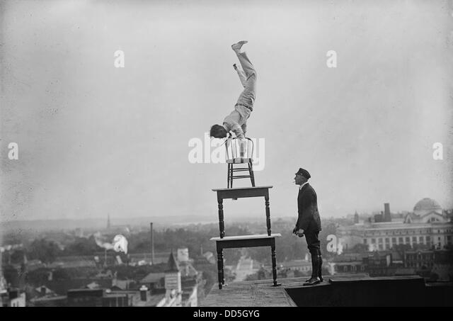 Jammie Reynolds, balancing on the on chairs on the edge of a rooftop in Washington, DC ca. 1921 - Stock-Bilder