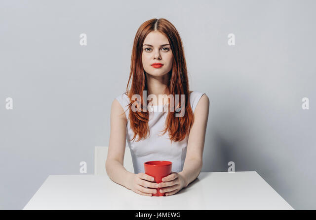 Caucasian woman sitting at table holding red cup - Stock-Bilder
