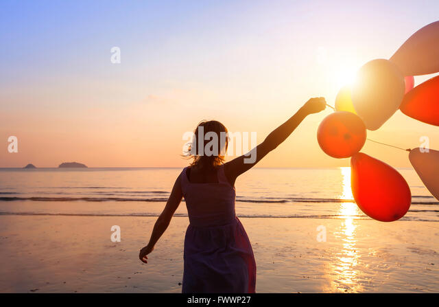 happiness concept, happy girl with multicolored balloons, joy and positive emotions - Stock Image
